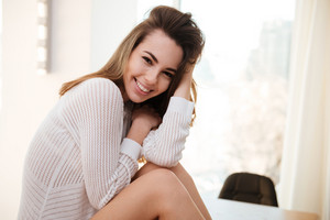 Portrait of a smiling young woman in sweater sitting at home