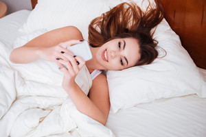 Portrait of a smiling young woman lying in bed and typing message on mobile phone