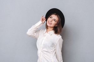 Portrait of a smiling young woman posing in hat and looking up over white background