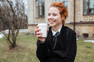 Portrait of a smiling young woman student drinking coffee to go while standing at the university campus