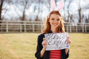 Portrait of a smiling young woman with red hair and rabbit ears holding happy easter board outdoors