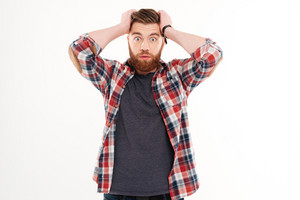 Portrait of a surprised bearded man with hands on head isolated on a white background