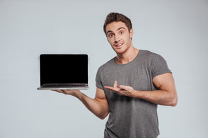 Portrait of a surprised casual man pointing on blank screen laptop over white background