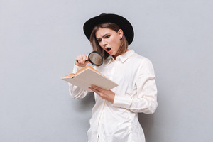 Portrait of a surprised focused woman reading book and using magnifying glass over gray background