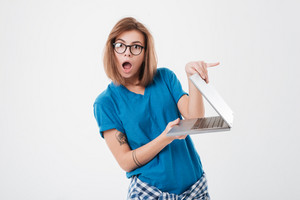 Portrait of a surprised young girl in eyeglasses opening laptop computer isolated on a white background
