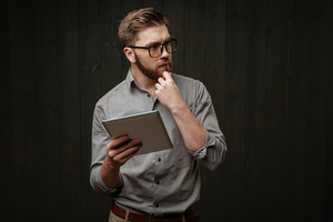 Portrait of a thoughtful bearded man using tablet computer isolated on a black wooden background