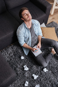 Portrait of a thoughtful young man sitting on a carpet with eyes closed and holding notepad