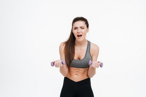 Portrait of a tired young sportswoman doing intensive training with dumbbells isolated on a white background