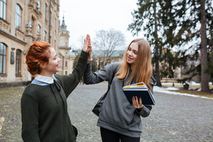 Portrait of a two young girl students giving high five outside the campus