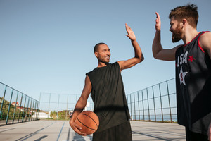 Portrait of a two young sports men giving high five while playing basketball at the playground