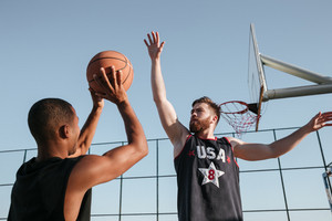 Portrait of a two young sports men playing basketball at the playground
