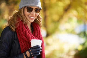 Portrait of a woman drinking coffee in autumn