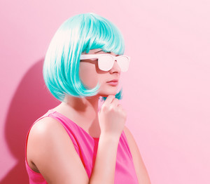 Portrait of a woman in a bright blue wig on a pink background