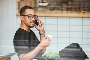 Portrait of a young afro american man in eyeglasses talking on mobile phone and drinking coffe while sitting in cafe, view through the window