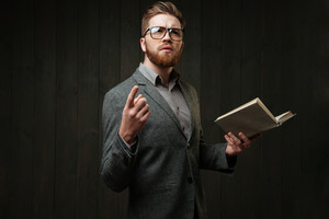 Portrait of a young bearded man in eyeglasses and casual suit learning script isolated on the black wooden background