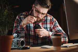 Portrait of a young bearded man repairing an old camera at his workplace