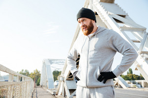 Portrait of a young bearded sports man in hat resting after workout outdoors at the bridge