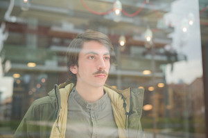 Portrait of a young beautiful caucasian man with moustache behind a showcase overlooking left - freshness, serene, carefree concept