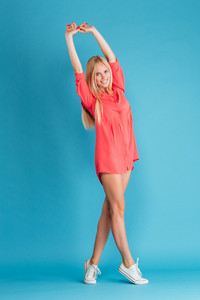 Portrait of a young blonde woman standing and stretching hands over blue background