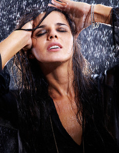 Portrait of a young brunette taking pleasure in rain
