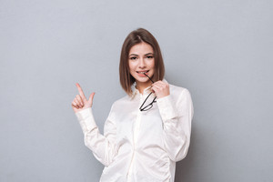 Portrait of a young brunette woman pointing finger up over white background