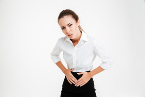 Portrait of a young businesswoman with stomach pain and looking at camera over white background