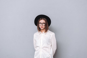 Portrait of a young casual girl wearing hat and eyeglasses standing over gray background