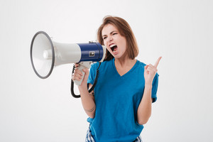 Portrait of a young casual woman screaming in megaphone and pointing finger up isolated on a white background