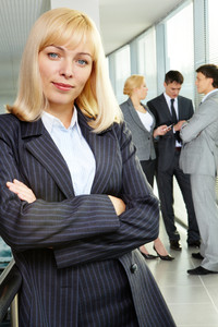 Portrait of a young confident businesswoman looking at camera with working team on background