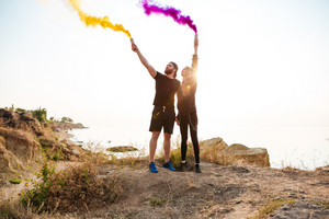 Portrait of a young couple holding colorful smoke bombs while standing outdoors