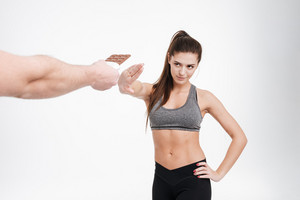 Portrait of a young determined fitness woman refusing to take chocolate from somebodys hand isolated on a white background