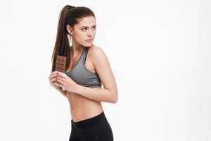 Portrait of a young fitness woman holding chocolate and looking over her shoulder isolated on a white background