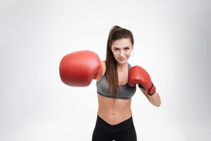 Portrait of a young fitness woman punching the camera with boxing gloves isolated on a white background
