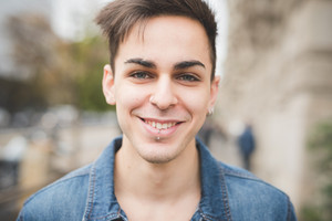 Portrait of a young handsome alternative dark model man looking in camera with central labret piercing smiling - youth, rebellion,diversity concept