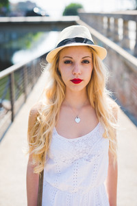 Portrait of a young handsome blonde straight long hair woman outdoor in the city, looking in camera, smiling with nostril piercing - freshness, carefreeness, youth concept