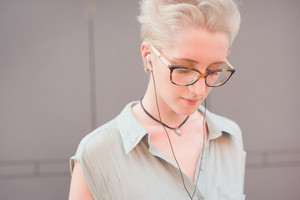 Portrait of a young handsome caucasian blonde italian designer listening music with earphones, looking downward - wearing speckled glasses and azure dress - relaxing concept