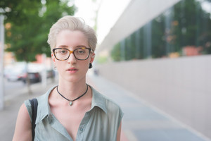 Portrait of a young handsome caucasian blonde italian designer posing in the city, looking in camera, serious - wearing a speckled pair of glasses and an azure dress - seriousness, pensive concept