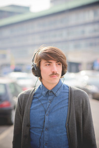 Portrait of a young handsome caucasian man with moustache listening music with headphones overlooking left- relax, carefreeness, youth concept