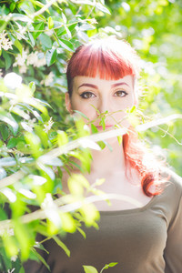 portrait of a young handsome caucasian redhead woman posing in a city park, seen through foliage looking in camera, serene - serenity, carefreeness concept - wearing green shirt