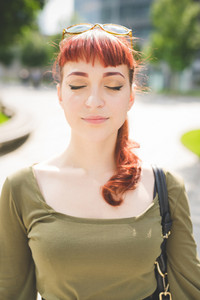 Portrait of a young handsome caucasian redhead woman with eyes closed, serene - serenity, carefreeness concept - wearing green shirt