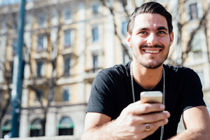 Portrait of a young handsome italian boy using a smartphone connected online - technology, social network concept