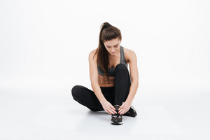 Portrait of a young healthy sporty woman sitting on the floor with her legs crossed and tying her shoelace isolated on a white background