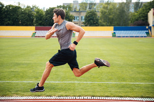 Portrait of a young male athlete training on a race track at the stadium