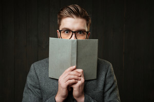 Portrait of a young man in eyeglasses covering face with book isolated on the black wooden background
