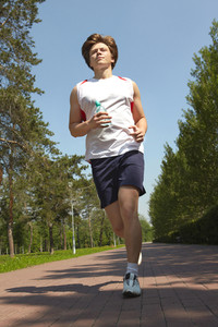 Portrait of a young man jogging in park in summer