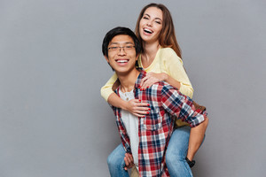 Portrait of a young multiracial couple enjoying piggyback ride isolated on the gray background