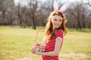 Portrait of a young pretty red head woman walking in park with basket and hunting for easter eggs