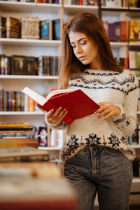 Portrait of a young pretty woman standing and reading book in library