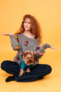 Portrait of a young red hair woman holding copy space on her palms while sitting with dog isolated on orange background