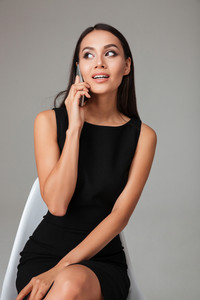 Portrait of a young smart businesswoman in black dress sitting and talking on mobile phone over gray background